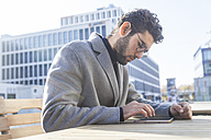 Young man sitting on bench using mini tablet - TCF05248