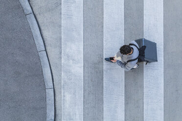 Businessman with baggage crossing the street while looking at cell phone, top view - TCF05251