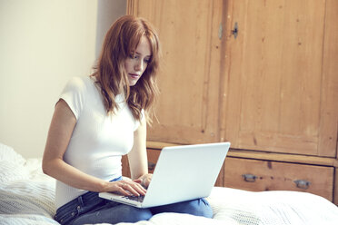 Redheaded woman sitting on bed using laptop - SRYF00158