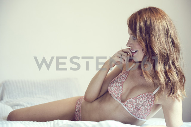 Smiling redheaded woman wearing lingerie lying on bed - SRYF00164