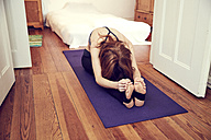 Redheaded woman doing stretching exercise at home - SRYF00176