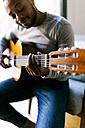 Young man at home playing guitar - VABF00954