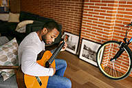 Young man at home playing guitar - VABF00957