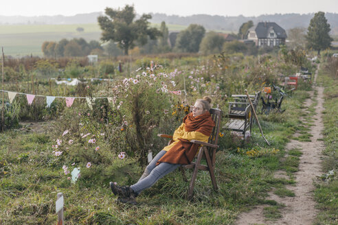 Young woman relaxing in cottage garden - KNSF00717