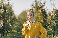 Young woman eating an apple in apple orchard - KNSF00729