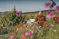Young woman relaxing in cottage garden - KNSF00741