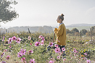 Young woman with spade in cottage garden - KNSF00753