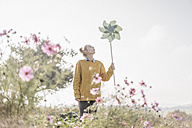 Young woman with pinwheel in cottage garden - KNSF00759