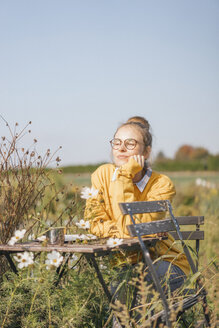 Young woman relaxing in cottage garden - KNSF00765