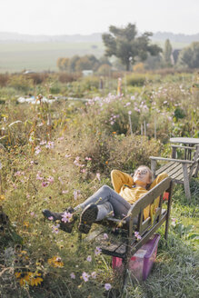 Young woman relaxing in cottage garden - KNSF00777
