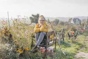 Young woman relaxing in cottage garden - KNSF00780