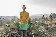Smiling young woman holding watering can in cottage garden - KNSF00789