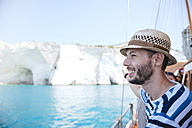 Greece, Milos, Man with straw hat on sailing boat - GEMF01319