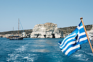 Greece, Milos, Greek boat flag at Kleftiko Beach - GEMF01322