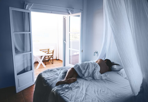 Greece, Milos, Woman sleeping in white sheets with open balcony door - GEMF01328