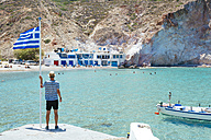 Greece, Milos, Firopotamos Beach, man looking at sea, holding onto Greek flag - GEMF01331