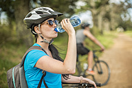 Young couple mountainbiking in nature, woman drinking water - ZEF11876
