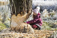 Girl touching tree trunk in winter - SARF03099