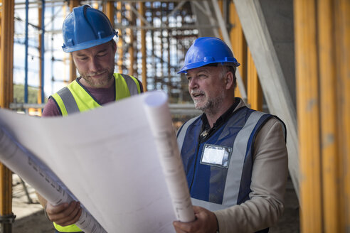 Engineers on construction site discussing blueprint - ZEF11885
