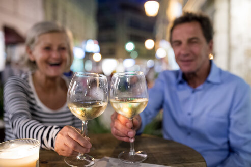 Senior couple drinking wine at an outdoor bar - HAPF01255