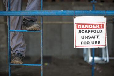 Construction worker climbing scaffold ladder - ZEF11967