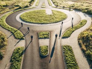 Multiple businessmen walking in roundabout - KNSF00800