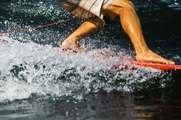 Indonesia, Bali, legs of surfer on a wave - KNTF00594