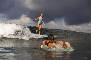 Indonesia, Bali, two women surfing - KNTF00600