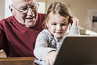 Grandfather and granddaughter using laptop together - UUF09538