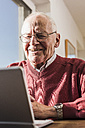Senior man sitting at home, using laptop - UUF09544