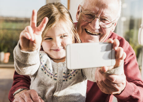 Grandfather and granddaughter taking selfies with a smart phone - UUF09547