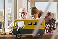 Grandfather and granddaughter assembling toy bus - UUF09550