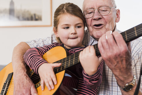 Grandfather and granddaughter playing together guitar - UUF09553