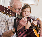 Grandfather and granddaughter playing together guitar - UUF09556