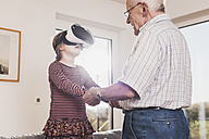 Grandfather holding granddaughter, using VR glasses - UUF09562