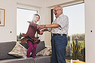 Grandfather and granddaughter jumping and dancing on couch - UUF09565