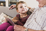 Grandfather reading out story for his granddaughter, using ebook - UUF09574