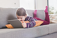 Little girl using digital tablet, lying on couch - UUF09577