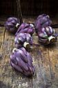 Purple organic artichokes on dark wood - LVF05741