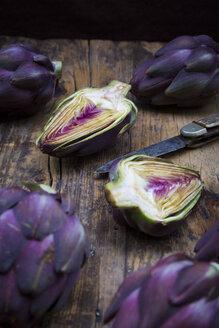 Sliced and whole purple organic artichokes and a pocket knife on dark wood - LVF05744