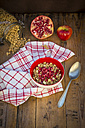 Bowl of granola with pomegranate seed and red apple on wood - LVF05752