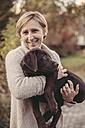 Woman holding Labrador Retriever - MFF03396