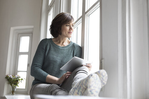 Woman with tablet looking out of window - RBF05342