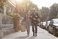 Smiling mature couple walking on pavement - RBF05351