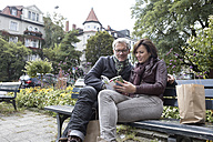 Mature couple with book sitting on bench - RBF05357