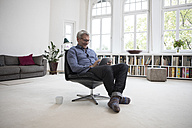 Mature man at home sitting in chair using tablet - RBF05372