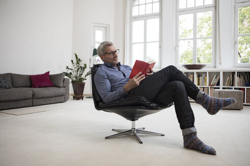 Mature man at home sitting in chair reading book - RBF05375