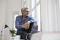 Relaxed mature man at home looking out of window - RBF05378