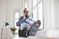 Mature man at home sitting at the window using tablet and cell phone - RBF05381