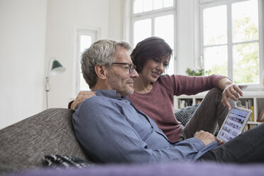 Mature couple at home on the sofa sharing tablet - RBF05390